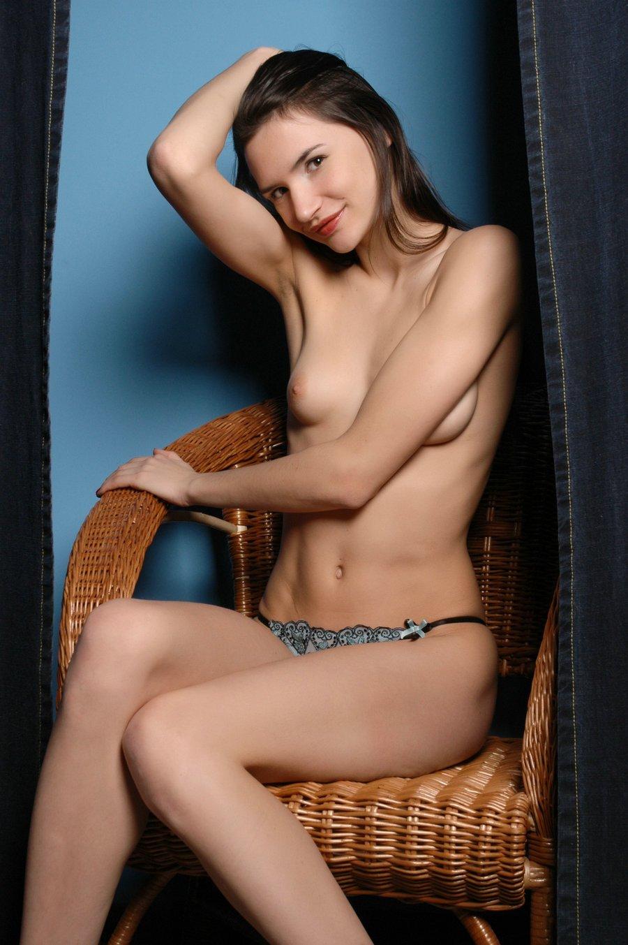 蓝色背景棚拍藤椅上的长头发嫩模
